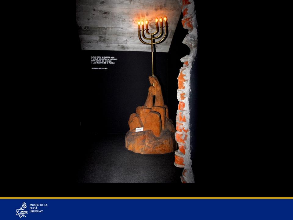 Candelabro de seis brazos que representa los seis millones de judíos asesinados en la Shoá, incluyendo un millón y medio de niños. Dentro del hueco donde se encuentra la foto ampliada de Elie Wiesel también hay una escultura en madera que tiene 6 lápidas. Sobre ellas hay un par de brazos fuertes en alto que sostienen un candelabro con 6 luminarias. Las luminarias son muy simbólicas para el pueblo de Israel: el candelabro de 7 brazos representa a nuestro pueblo, el candelabro con 8 brazos representa a la festividad de Jánuca, las 2 o más velas el Shabat, (la víspera del sábado). En esta escultura vemos un candelabro con 6 luminarias representando a los 6 millones de judíos asesinados por el nazismo entre ellos 1.500.000 de niños. Cómo imaginar esa cifra si cuando se lastima a un solo niño nos duele a todos. Fueron seres inocentes cuyo único pecado fue nacer, nacer judíos. Cuántas generaciones fueron truncadas por esos asesinatos… Se estima que no fueron 6.000.000 sino 10 o 12.000.000 las pérdidas en vidas judías, por las generaciones que no nacieron de los 6.000.000. Precisamente las primeras fotos del museo son de niños.