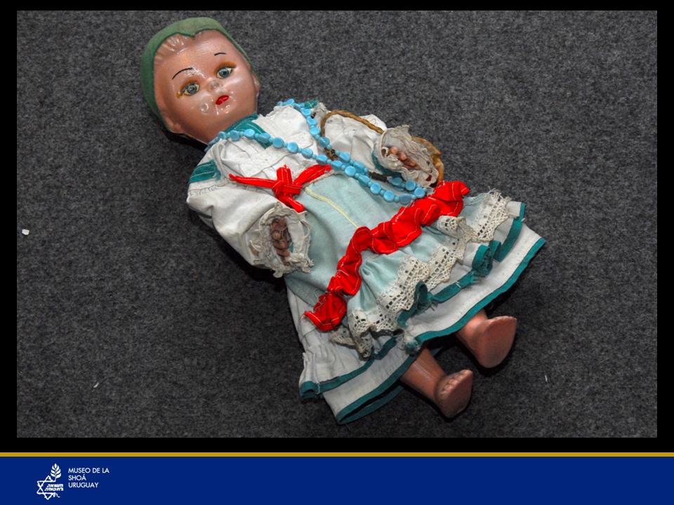 La Sra. María Klein estuvo en el ghetto de Ginta-Rumania donde hacía trabajos forzados y siempre conservó como tesoros preciados, esta muñeca y su libro de rezos. La muñeca la conservaba con cariño, como si fuera la hija que nunca tuvo.