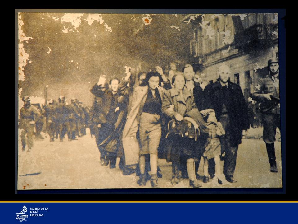 Se ven judíos que se entregaron después que fue bombardeado el ghetto de Varsovia. Antes lucharon heroicamente durante casi cinco semanas y lograron tener en jaque a los nazis durante ese período, con muy pocas armas, lo cual fue extraordinario. En el ghetto de Varsovia sí había información y sabían que lo que les esperaba era la muerte en los campos de concentración y un grupo de valientes prefirió luchar hasta morir, comandados por Mordejai Anilevich. En Varsovia había polacos patriotas que querían enfrentarse a los nazis y apoyaron a los judíos de esa ciudad. Les pasaban información introduciéndose al ghetto a través de las cloacas. Y así pudieron elaborar armas caseras para defenderse de los nazis. Luego de esas 5 semanas los nazis decidieron finalmente bombardear todo el ghetto y así triunfaron. En otros ghettos no había información alguna y ni imaginaban cuál sería su destino, por lo que había menor resistencia.