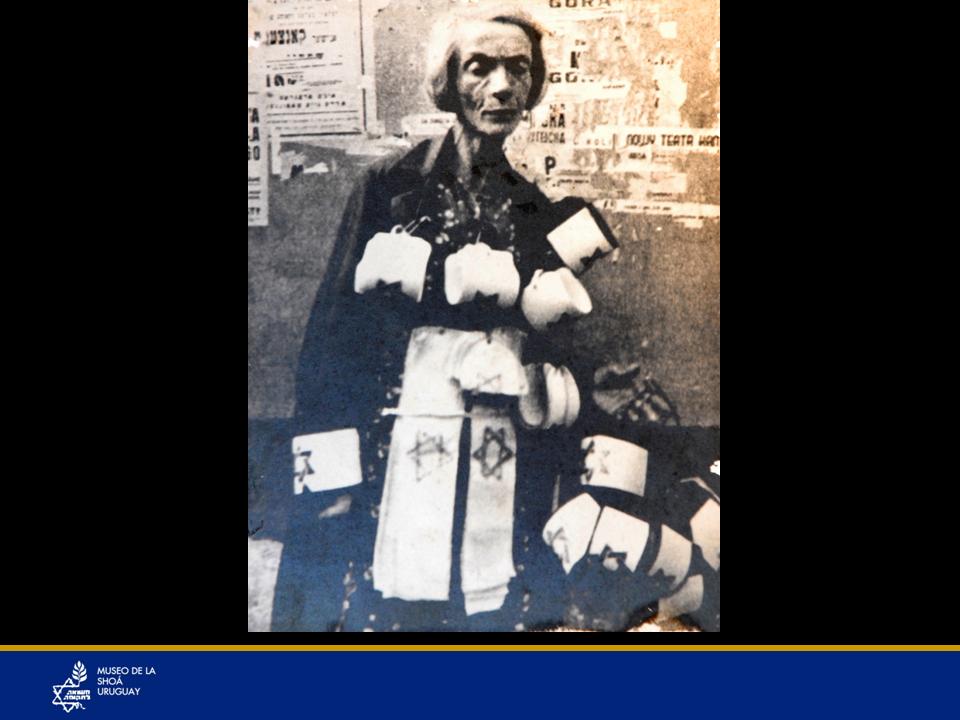 Una vendedora de brazaletes en el ghetto de Varsovia, un brazalete blanco con la estrella de David en azul. En otros ghettos se utilizaba una estrella amarilla en el pecho y otra en la espalda.