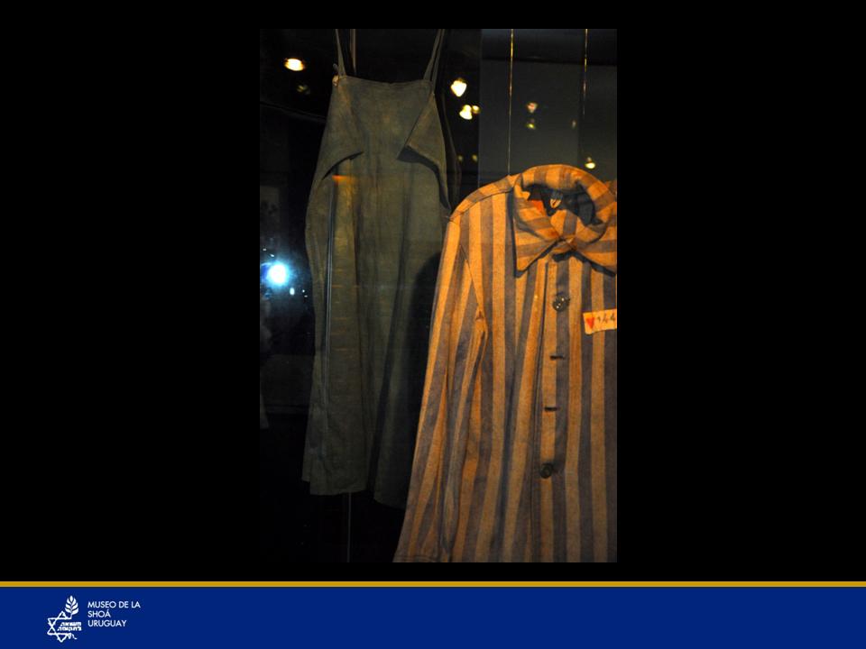 Vestido Rosa Filut. Donación Shai Steinhaus. Rosa Filut nació en Polonia. Estaba en un campo de trabajos forzados en Rusia trabajando con tanques de guerra y en la parte trasera de los tanques había tela y ella tomó trozos de esa tela y cosiendo como pudo, confeccionó un vestido que usaba bajo el uniforme con riesgo de perder la vida por hacerlo.